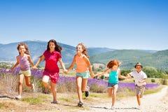 Счастливые дети бежать совместно через поле лаванды Стоковое фото RF