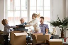 Счастливые дети воюя коробки упаковки подушек совместно на двигать Стоковое Изображение