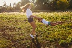 Счастливые дети держа руки в лете на заходящем солнце Стоковое фото RF