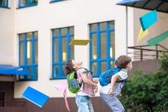Счастливые дети - 2 друз с книгами и рюкзаками на первом или последним учебным днем Стоковые Изображения RF