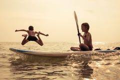 Счастливые дети играя на пляже на времени дня Стоковая Фотография RF
