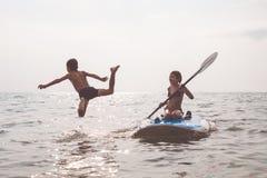 Счастливые дети играя на пляже на времени дня Стоковые Фото