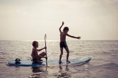 Счастливые дети играя на пляже на времени дня Стоковое Изображение RF