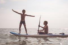 Счастливые дети играя на пляже на времени дня Стоковые Изображения