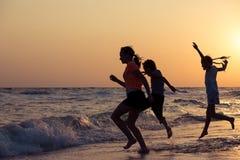 Счастливые дети играя на пляже на времени захода солнца Стоковая Фотография