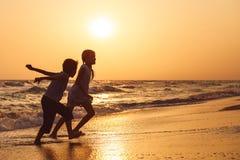 Счастливые дети играя на пляже на времени захода солнца Стоковые Фотографии RF