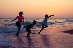 Счастливые дети играя на пляже на времени захода солнца Стоковое Изображение