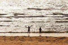 Счастливые дети играя на пляже на заходе солнца стоковые фотографии rf