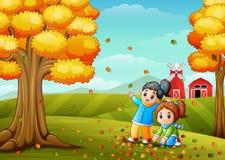 Счастливые дети играя с листьями осени Стоковое фото RF