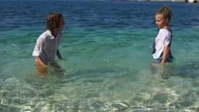 Счастливые дети имеют потеху в ясной морской воде Мальчик и выплеск и смех девушки акции видеоматериалы