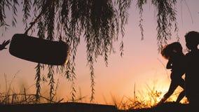 Счастливые дети имея потеху внешнюю Мальчик и девушка играя с качанием около озера во время красивого захода солнца акции видеоматериалы