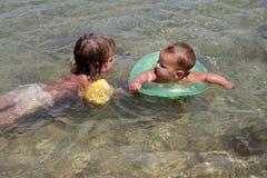 Счастливые дети имея потеху в воде Стоковые Изображения