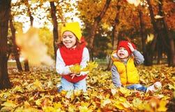 Счастливые дети мальчик и девушка имея потеху в осени стоковое изображение