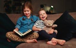 Счастливые дети мальчик и девушка читая книгу в вечере в темноте стоковая фотография rf