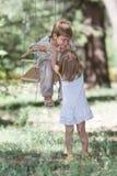 Счастливые дети на качании на естественной предпосылке Стоковое Фото