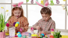 Счастливые дети нося уши зайчика крася яйца на день пасхи сток-видео