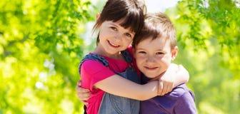 Счастливые дети обнимая над зеленой естественной предпосылкой Стоковые Фотографии RF