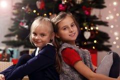 Счастливые дети представляя перед рождественской елкой Стоковое фото RF