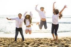Счастливые дети скача совместно на пляж стоковые изображения rf