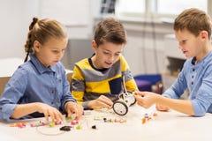 Счастливые дети строя роботы на школе робототехники Стоковое Фото