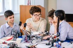 Счастливые дети учат программирование используя компьтер-книжки на внеучебных классах стоковое изображение