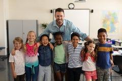 Счастливые дети школы и класс положения учителя стоковое изображение rf