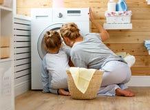 Счастливые домохозяйка и ребенок матери семьи в прачечной с washin стоковые фото