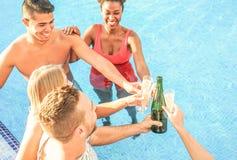 Счастливые друзья веселя с шампанским в бассейне - молодые люди имея потеху делая партию и провозглашая тост стекла prosecco стоковая фотография rf