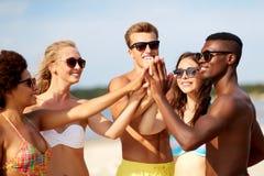 Счастливые друзья делая высоко 5 на пляже лета стоковое фото rf