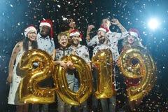 Счастливые друзья держа символ 2019 год на партии стоковые фото