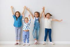 Счастливые друзья детей вокруг пустых стен стоковая фотография rf