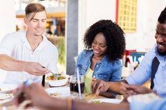 Счастливые друзья есть на ресторане Стоковое Фото