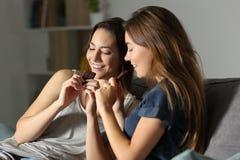 Счастливые друзья есть шоколад в ноче Стоковое Изображение RF
