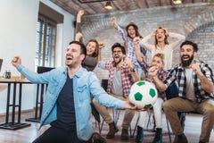 Счастливые друзья или футбольные болельщики смотря футбол на ТВ Стоковое Изображение RF