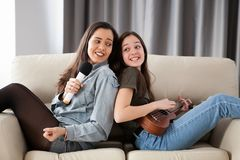 Счастливые друзья имея большое время на кресле в живущей комнате Стоковое фото RF