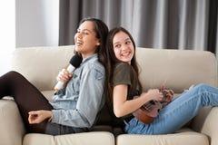 Счастливые друзья имея большое время на кресле в живущей комнате Стоковое Изображение RF