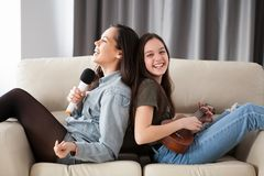 Счастливые друзья имея большое время на кресле в живущей комнате Стоковые Изображения