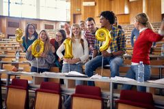Счастливые друзья имея партию в университете стоковое фото
