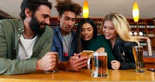Счастливые друзья используя мобильный телефон пока имеющ стекло пива 4k акции видеоматериалы