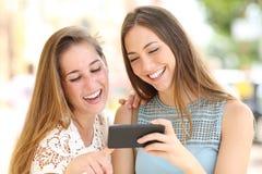 Счастливые друзья наблюдая средства массовой информации на смартфоне в улице стоковые изображения rf