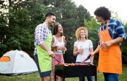 Счастливые друзья наслаждаясь партией барбекю и гриля на открытом воздухе стоковые изображения rf