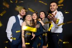 Счастливые друзья на партии под confetti над чернотой Стоковые Фото
