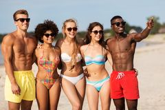 Счастливые друзья обнимая на пляже лета стоковые изображения