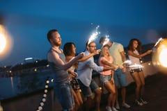 Счастливые друзья освещая бенгальские огни и наслаждаясь свободой Стоковое Изображение RF
