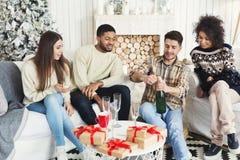 Счастливые друзья празднуя Новый Год с шампанским стоковое фото