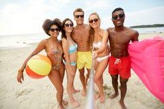 Счастливые друзья принимая selfie на пляже лета стоковая фотография