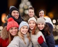 Счастливые друзья принимая selfie outdoors на рождество Стоковые Изображения RF