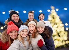 Счастливые друзья принимая selfie outdoors на рождество Стоковые Фото
