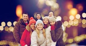 Счастливые друзья принимая selfie outdoors на рождество Стоковая Фотография RF