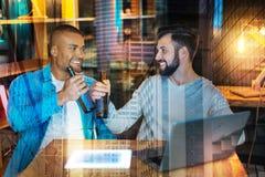Счастливые друзья сидя на таблице и усмехаясь пока выпивающ пиво Стоковые Фото